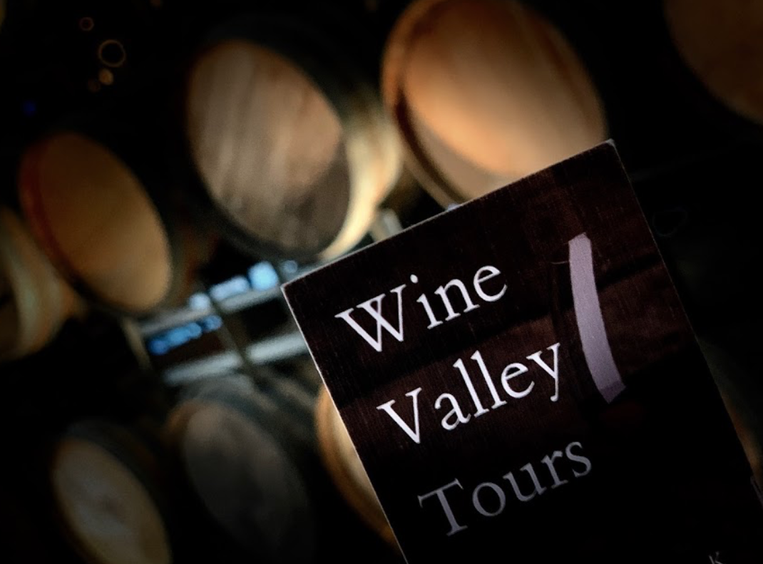 Wine Valley Tours business card with a great backdrop of oak wine barrels.